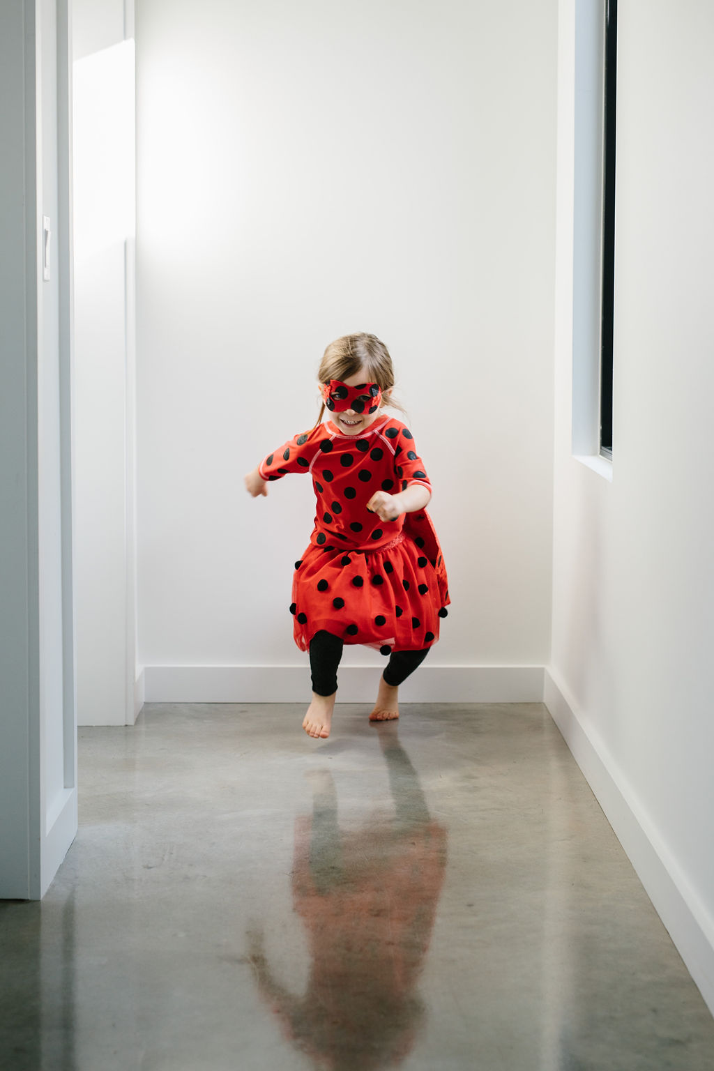 A child running in the miraculous ladybug costume