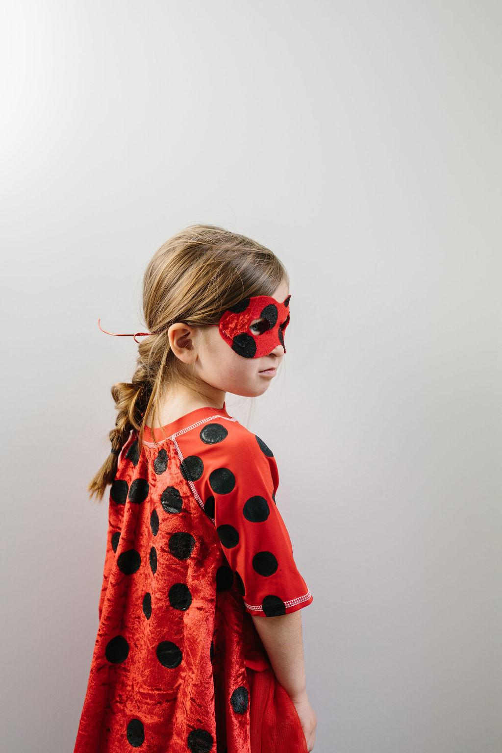 A little girl wearing a miraculous ladybug costume