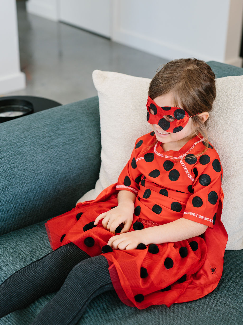 A girl in a costume sitting on a sofa