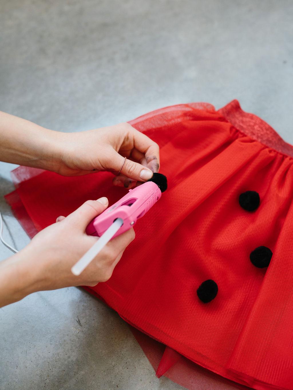 Glueing pom poms onto the miraculous ladybug costume