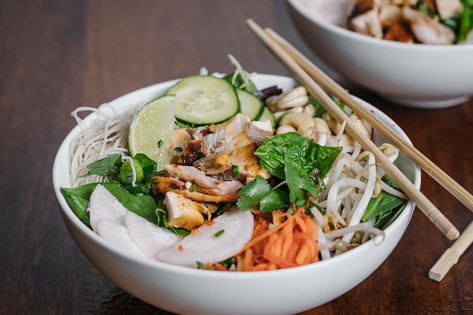 A fresh Vietnamese noodle bowl served on a wooden table