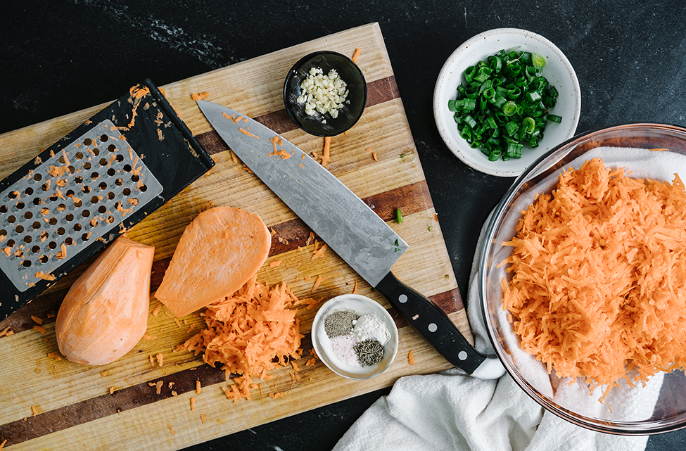 Shredded sweet potato on a wooden chopping board