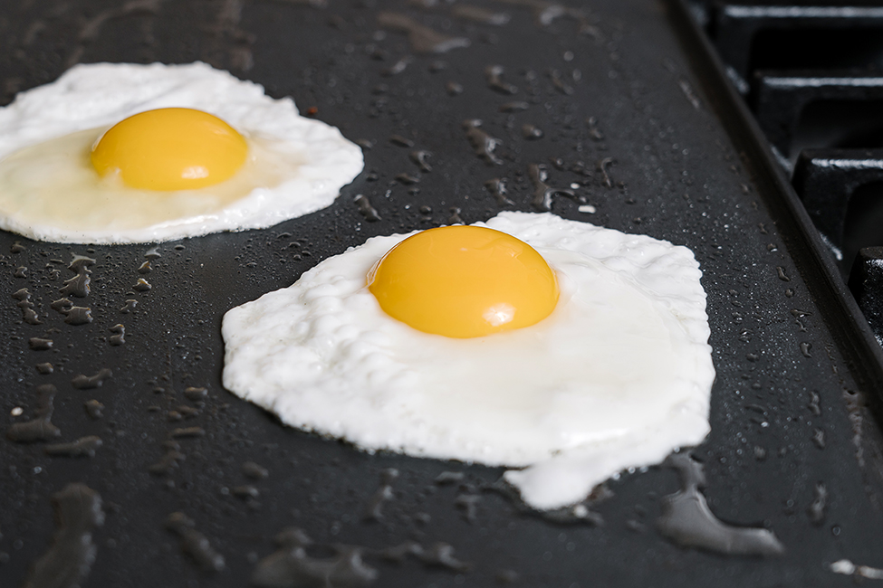 Two sunny side up eggs being cooked