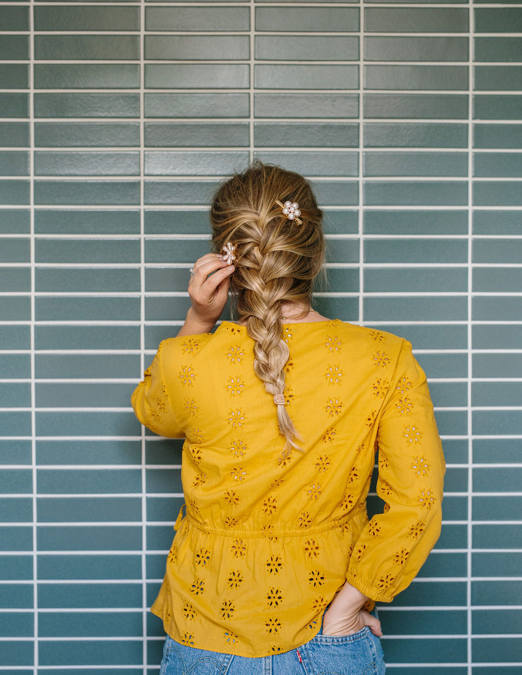 A women with a French braid touching the back of the hair