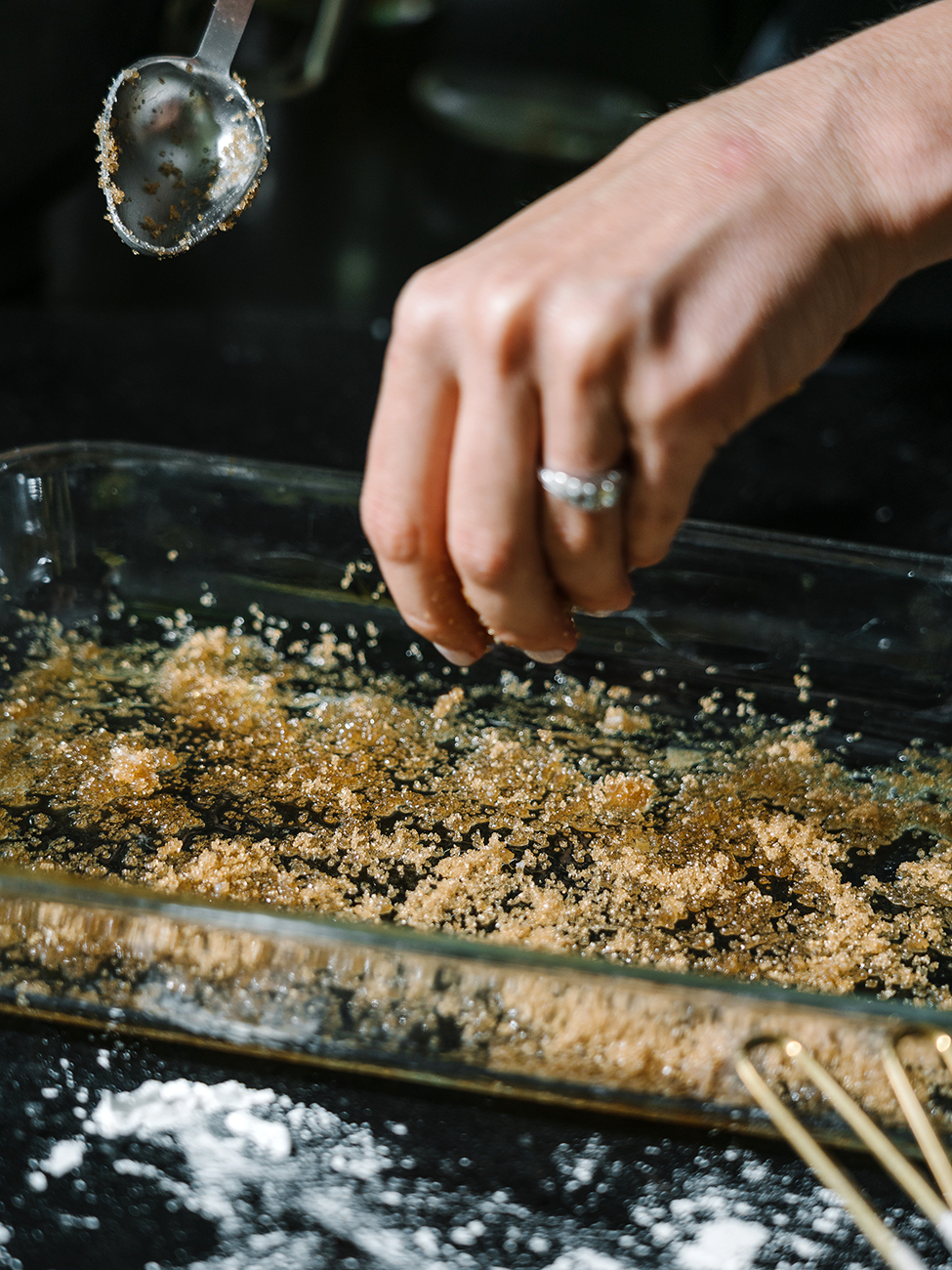 Sugar being sprinkled into a glass baking dish