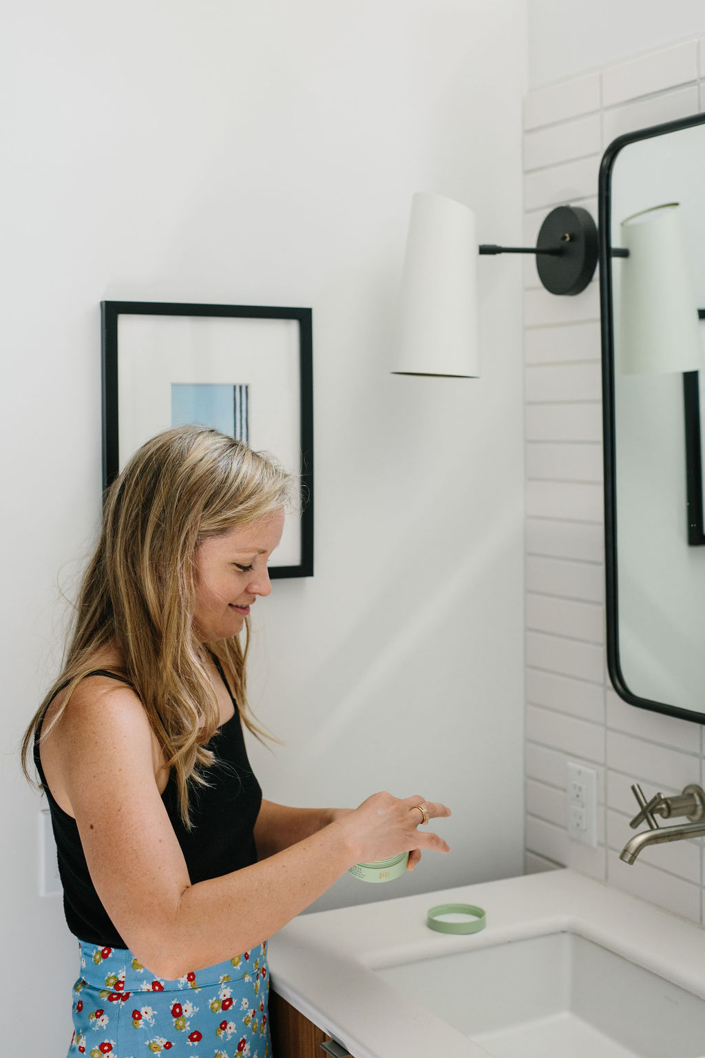 A woman standing in front of a mirror using Clean Beauty Products