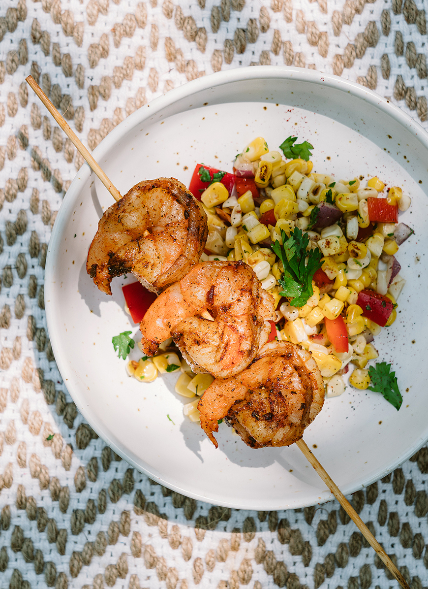 Grilled Shrimp served with corn salad on a white plate