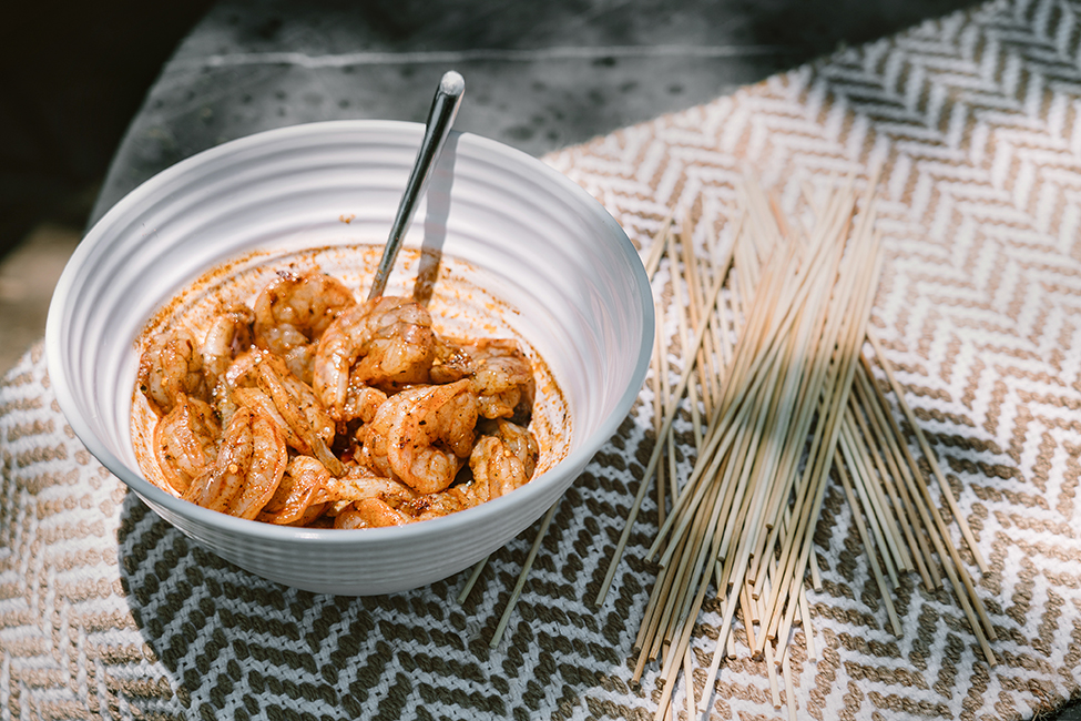 Shrimp marinating in a small white bowl