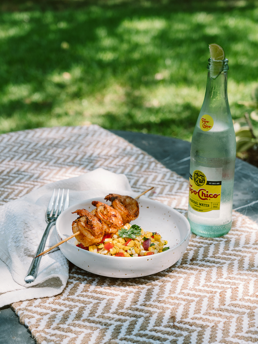 Grilled Shrimp and corn salad served on a table with a bottle of water