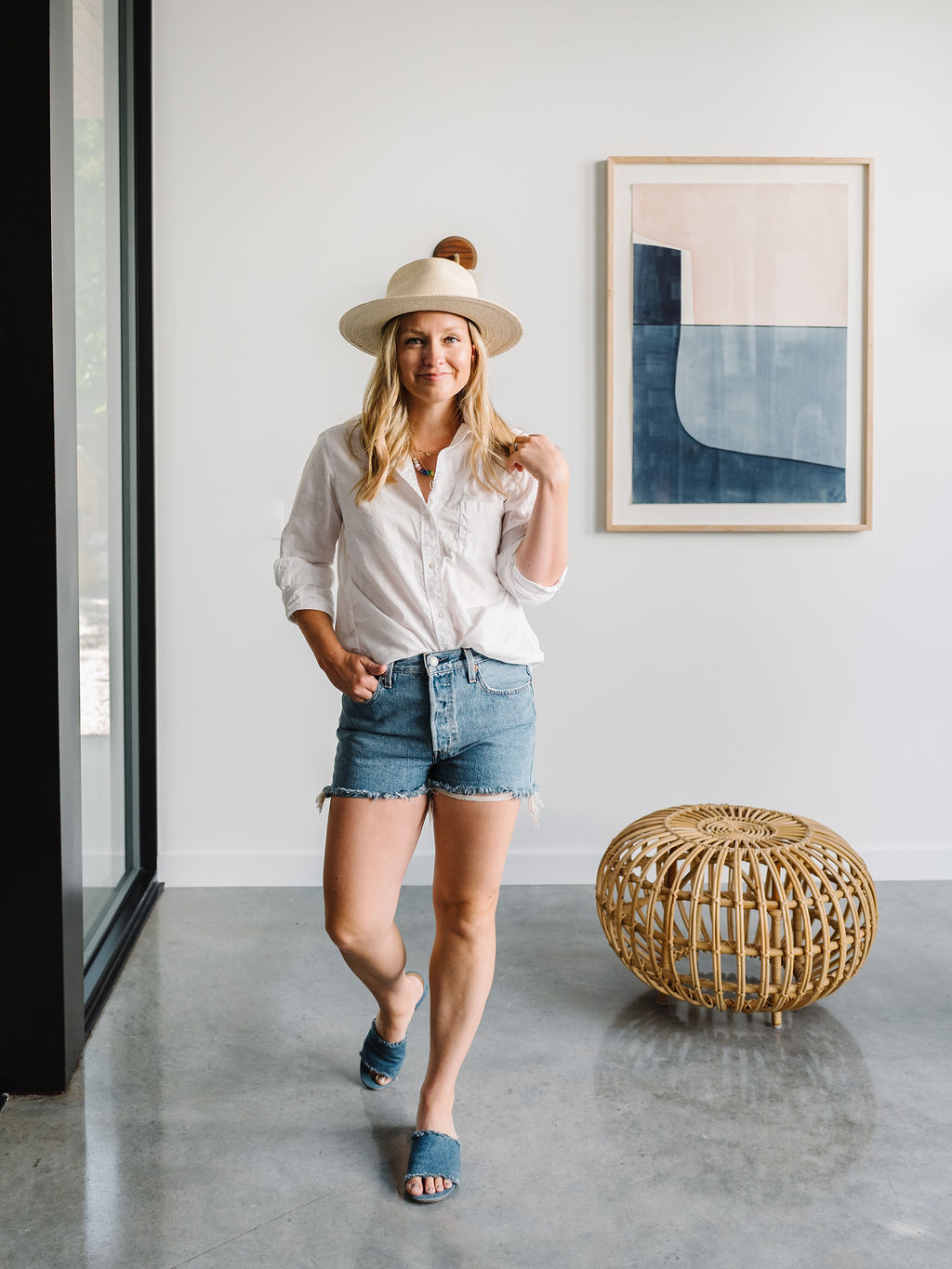 Woman wearing a hat, white shirt and denim jeans