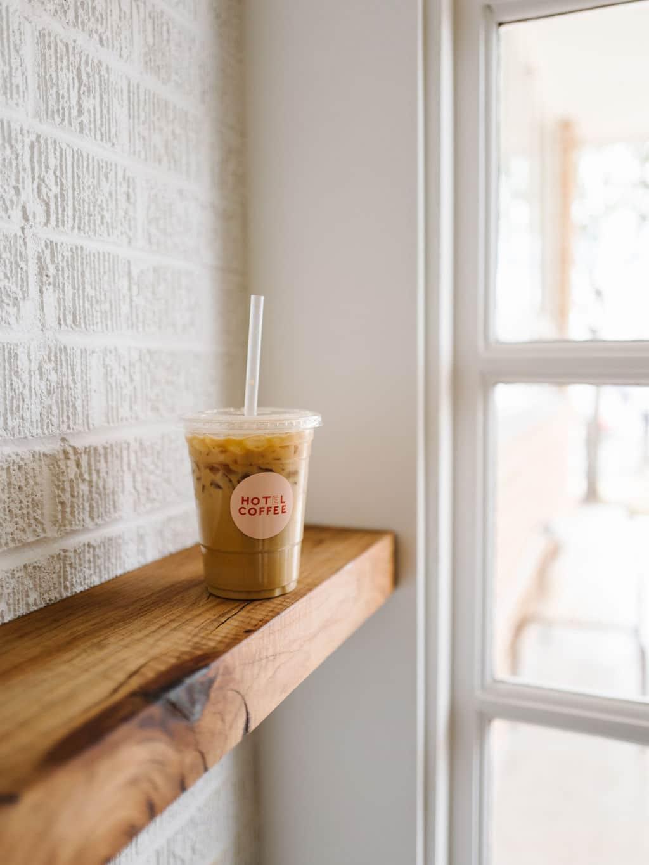 An iced coffee on a wooden bar