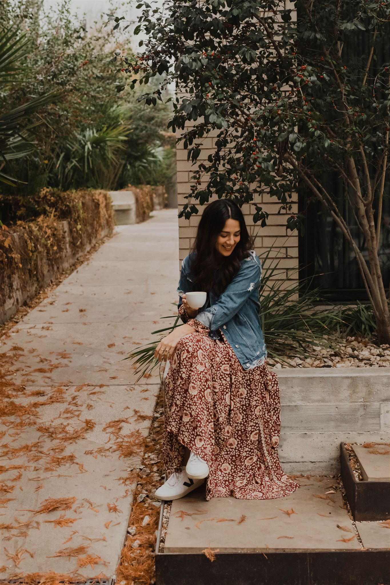 cristina bocanegra at south congress hotel exterior with autumn leaves in the background austin in floral dress with coffee cup
